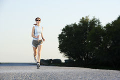Woman Running. A woman running down a path at the beach Royalty Free Stock Image