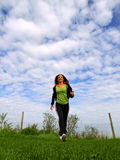 Woman running. Young woman running on grass to stay fit Royalty Free Stock Photography