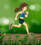 A woman running above a wood with leaves Royalty Free Stock Photo