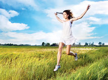 Woman running across field Royalty Free Stock Image