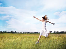 Woman running across field Stock Photo