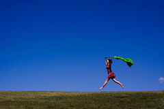 Woman running across a green landscape. Holding a sarong, an attractive woman runs joyfully bounding across this green field Royalty Free Stock Photography