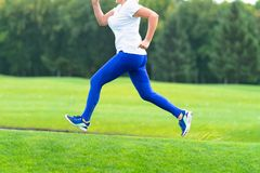 Woman running across large open grassy field stock images