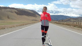 Woman running alone at beautiful sunset on the road. Autumn sport and freedom concept. Athlete training on dusk. 20s 4k. Woman running alone at beautiful sunset stock video