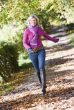 Woman running along autumn path. Looking to camera Royalty Free Stock Image