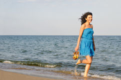 Woman running along the edge of the surf. Pretty woman running along the edge of the surf on a sandy beach with her shoes in her hand Stock Photography