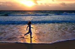 woman running  along ocean coast Stock Photography