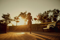 A woman is running along the road in the park. Stock Image