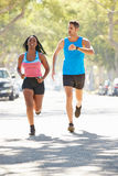 Woman Running Along Street With Personal Trainer royalty free stock photography