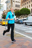 Woman Running Along Urban Street Royalty Free Stock Photography