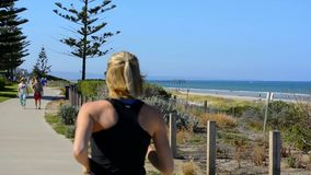 Woman running along walking track. Woman running and people exercising along new Henley Beach walking track overlooking scenic views of beach, handheld, slow stock video footage