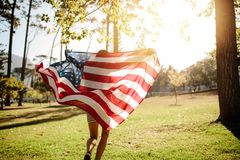 Woman running with american flag in park. Woman running with american flag on a sunny day. Shot from behind of a girl running in the park with American flag royalty free stock image
