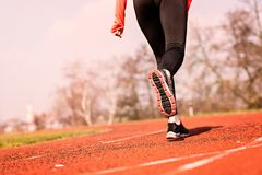 Woman running around the track on a sunny spring day. Stock Image