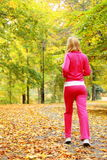 Woman running in autumn forest.  Female runner training. Stock Photos