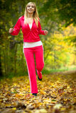 Woman running in autumn forest.  Female runner training. Stock Photo