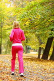 Woman running in autumn forest.  Female runner training. Stock Images