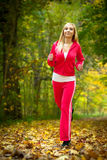 Woman running in autumn forest.  Female runner training. Royalty Free Stock Images