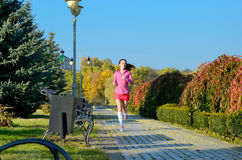 Woman running in autumn park, beautiful girl runner jogging Stock Photo