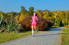 Woman running in autumn park, beautiful girl runner jogging. Outdoors, training for marathon, exercising and fitness concept Royalty Free Stock Photography