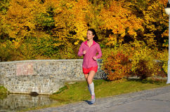 Woman running in autumn park, beautiful girl runner jogging Stock Images