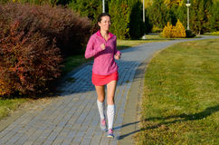 Woman running in autumn park, beautiful girl runner jogging outdoors Royalty Free Stock Images
