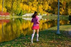 Woman running in autumn park, beautiful girl runner jogging outdoors Royalty Free Stock Photos