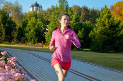 Woman running in autumn park, beautiful girl runner jogging outdoors Royalty Free Stock Photos