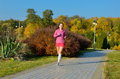 Woman running in autumn park, beautiful girl runner jogging outdoors. Training for marathon, exercising and fitness concept Royalty Free Stock Image