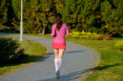 Woman running in autumn park, beautiful girl runner jogging outdoors Stock Images