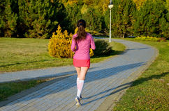 Woman running in autumn park, beautiful girl runner jogging outdoors Stock Photo