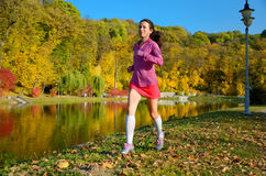 Woman running in autumn park, beautiful girl runner jogging outdoors Stock Image