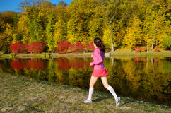 Woman running in autumn park, beautiful girl runner jogging outdoors. Training for marathon, exercising and fitness concept Royalty Free Stock Photos