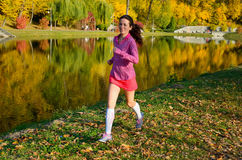 Woman running in autumn park, beautiful girl runner jogging outdoors. Training for marathon, exercising and fitness concept Stock Image
