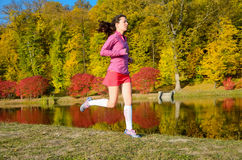 Woman running in autumn park, beautiful girl runner jogging outdoors Stock Photos
