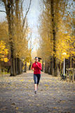 Woman running in autumn park Stock Photo