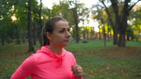 Close up of woman running through an autumn park at sunset stock video