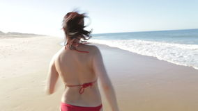 Woman Running Away From Camera On Beach Royalty Free Stock Photo