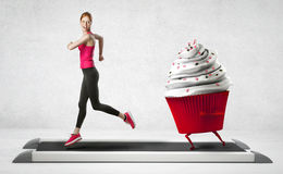 Woman running away from a cupcake Stock Photo