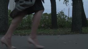 Woman is Running Away. In the evening on the street low angle feet view in slow motion gimbal shot stock footage