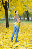 Woman Running Away With Leaves in Autumn Royalty Free Stock Image