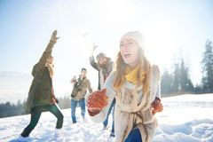 Snowball fight. Woman running away from the snow fight royalty free stock images