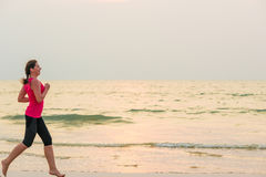 Woman running barefoot on the beach Royalty Free Stock Photos