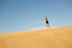 Woman running barefoot on sand desert dunes Stock Photos