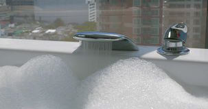 Woman running bath with foam. Close-up shot of woman turning on the tap to run a bath and she turning it off when bathtub is full of foam, window with city view stock footage