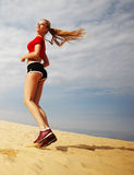 Woman running on beach. A young woman running on the beach Royalty Free Stock Photography