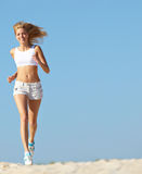 Woman running on beach stock photography