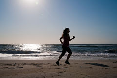 Woman running on the beach Stock Photos