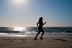 Woman running on the beach Stock Photos