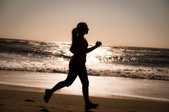 Woman running on the beach. A woman running on the beach at sunrise Stock Photography