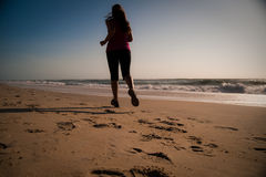 Woman running on the beach Royalty Free Stock Photos